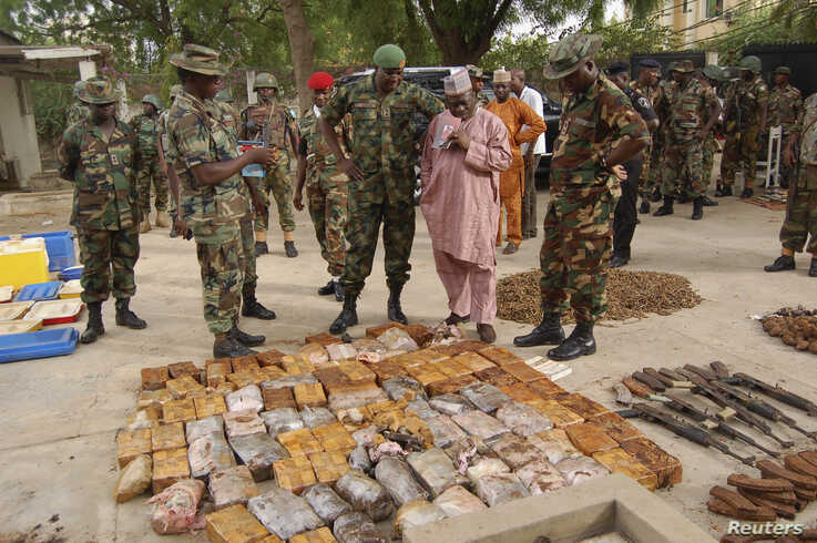 Military officials stand near ammunitions seized from suspected members of Hezbollah after a raid of a building in Kano, Nigeria, May 30, 2013.