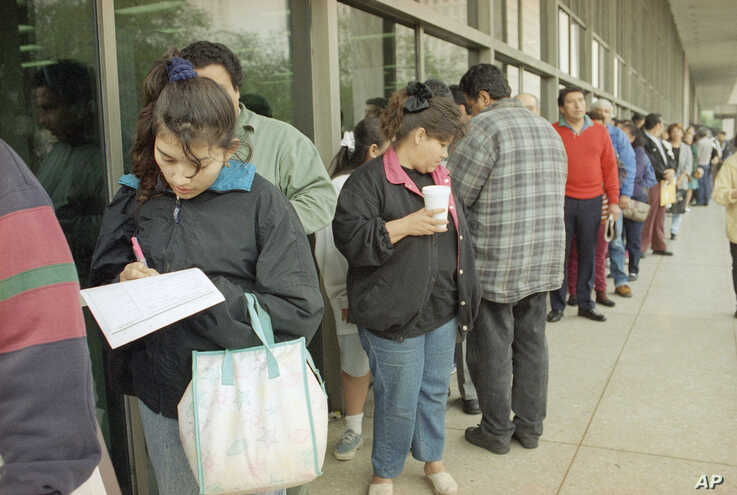 Mercedes Garcia of El Salvador fills in the application for her new ?green card? while waiting in a predawn line outside the Immigration and Naturalization Service office on Wednesday, March 20, 1996 in Los Angeles. Wednesday was the deadline to appl