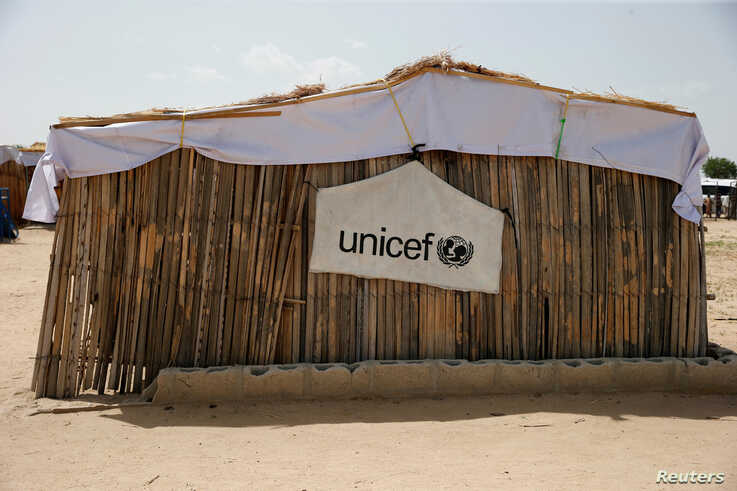 FILE PHOTO: A banner with the UNICEF logo is seen hanging on a makeshift school at an internally displaced persons  camp on the outskirts of Maiduguri, northeast Nigeria, June 6, 2017.