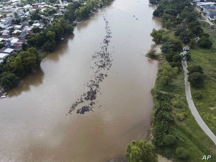 A new group of Central American migrants bound for the U.S border wade in mass across the Suchiate River, that connects Guatemala and Mexico, in Tecun Uman, Guatemala, Monday, Oct. 29, 2018.