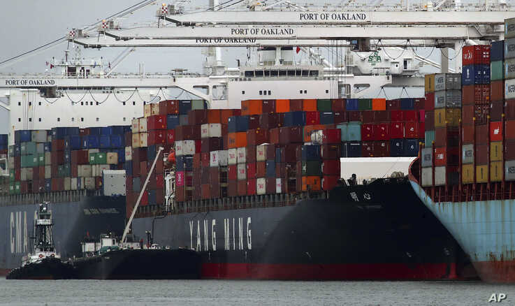 The Yang Ming shipping line container ship Ym Utmost is unloaded at the Port of Oakland on Monday, July 2, 2018, in Oakland, Calif. The Trump administration on Friday, July 6, 2018, will start imposing tariffs on $34 billion in Chinese imports.
