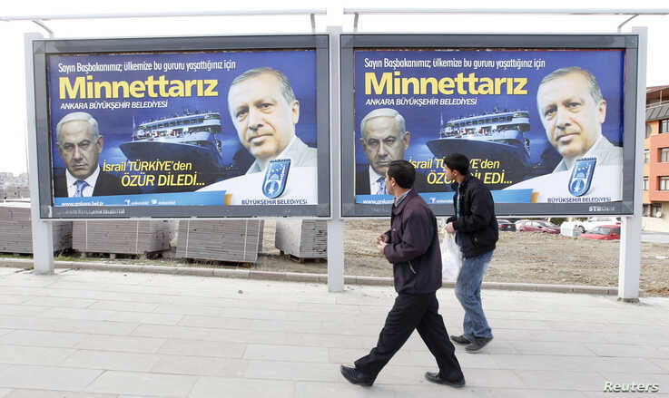 FILE - Pedestrians look at billboards with the pictures of Turkey's Prime Minister Tayyip Erdogan (R) and his Israeli counterpart Benjamin Netanyahu (L), in Ankara.