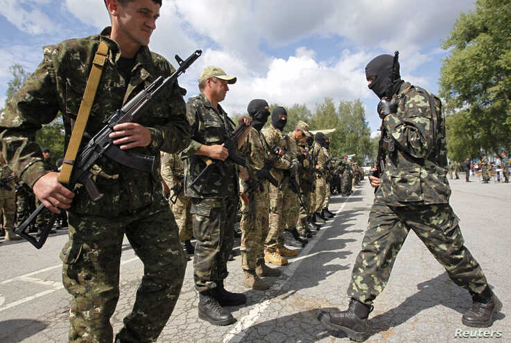 "Members of the ""Donbass"" self-defense battalion attend a ceremony to swear an oath to be included in a reserve battalion of the National Guard of Ukraine near Kyiv, June 23, 2014."