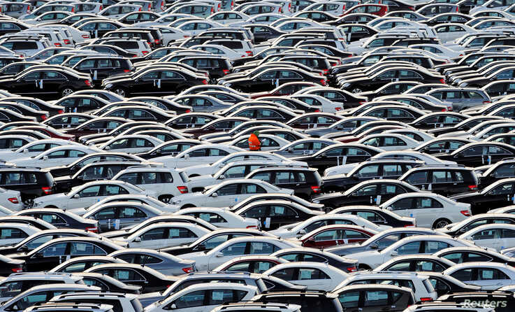 A worker walks along rolls of Mercedes cars at a shipping terminal in the harbor of the town of Bremerhaven, Germany, March 8, 2012.