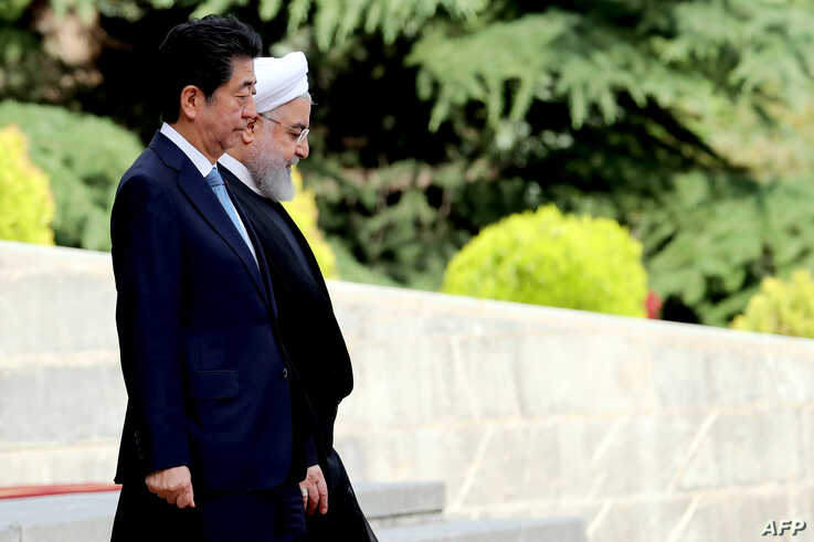 Iranian President Hassan Rouhani, right, welcomes Japanese Prime Minister Shinzo Abe, during a welcoming ceremony at the Saadabad Palace in the capital Tehran, June 12, 2019.