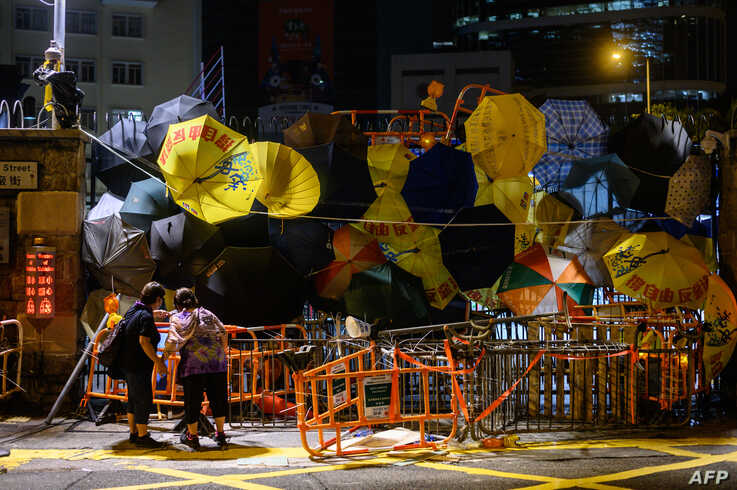 Two bystanders peer into barricades and umbrellas attached to an entry gate to the police headquarters in Hong Kong.