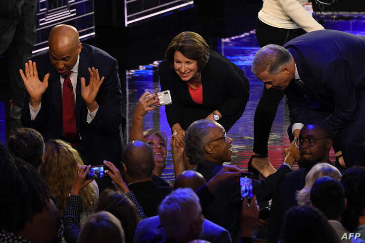 Democratic presidential hopefuls, from left, Cory Booker and Amy Klobuchar greet supporters as Jay Inslee greets US activist Al Sharpton after the first Democratic primary debate of the 2020 presidential campaign in Miami, June 26, 2019.