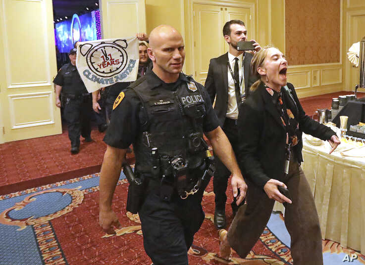 """About 25 protesters are escorted by police after interrupting a energy summit where U.S. Energy Secretary Rick Perry spoke, May 30, 2019, in Salt Lake City. Perry says the Trump administration is committed to making fossil fuels cleaner rather than imposing """"draconian"""" regulations on oil, gas and coal. Perry made his remarks during a speech at an energy conference in Salt Lake City hosted by Utah Gov. Gary Herbert. (AP Photo/Rick Bowmer)"""