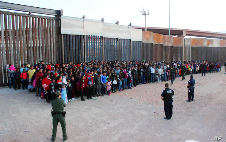 FILE - This May 29, 2019 file photo released by U.S. Customs and Border Protection (CBP) shows some of 1,036 migrants who crossed the U.S.-Mexico border in El Paso, Texas, the largest that the Border Patrol says it has ever encountered. The federal government is opening a new mass shelter for migrant children near the U.S-Mexico border and is considering housing children on three military bases to add 3,000 more beds to the overtaxed system in the coming weeks. (U.S. Customs and Border Protection via AP, Fi