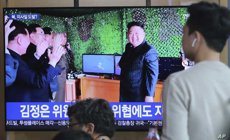 FILE - In this May 5, 2019, photo, people watch a TV showing a photo of North Korean leader Kim Jong Un during a news program reporting a North Korean missile launch, at the Seoul Railway Station in Seoul, South Korea. North Korea tested two more mis...