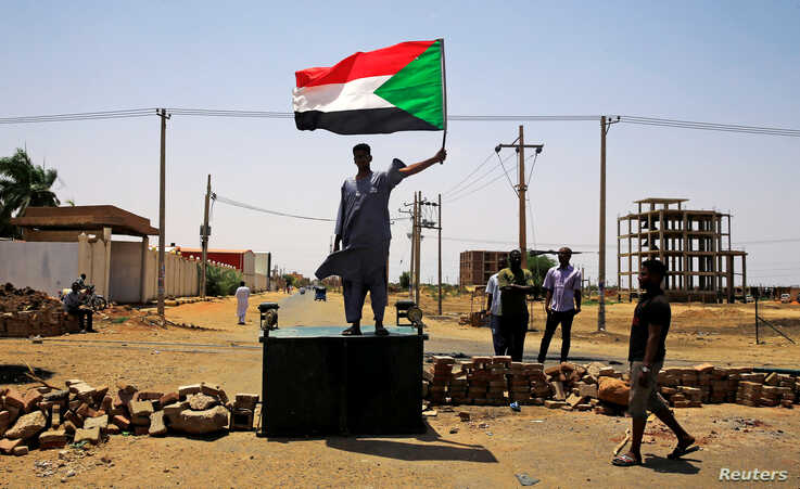 A Sudanese protester holds a national flag as he stands on a barricade along a street, demanding that the country's Transitional Military Council hand over power to civilians, in Khartoum, Sudan June 5, 2019. REUTERS/Stringer     TPX IMAGES OF THE DAY - RC1B85AE3F50