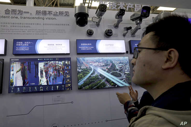 FILE - An man looks at technologies from state-owned surveillance equipment manufacturer Hikvision on a monitor at a Security China 2018 expo in Beijing, Oct. 23, 2018.