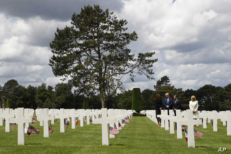 President Donald Trump, first lady Melania Trump, French President Emmanuel Macron and Brigitte Macron, walk through The Normandy American Cemetery, following a ceremony to commemorate the 75th anniversary of D-Day, June 6, 2019, in Colleville-sur-Mer, No