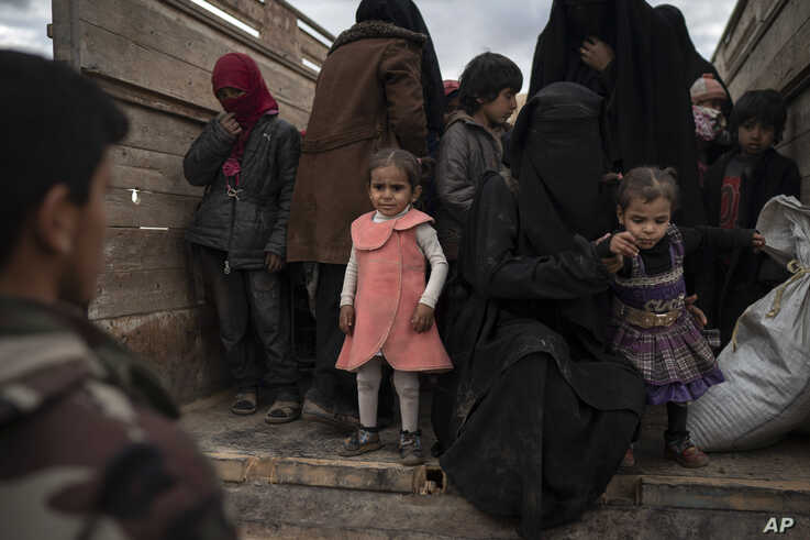 Women and children exit the back of a truck to be screened by U.S.-backed Syrian Democratic Forces (SDF) after being evacuated out of the last territory held by Islamic State militants, in the desert outside Baghouz, Syria, Wednesday, Feb. 27, 2019. (AP Photo/Felipe Dana)