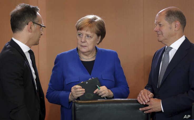 German Chancellor Angela Merkel, center, German Foreign Minister Heiko Maas, left, and German Finance Minister Olaf Scholz talk as they arrive for the weekly cabinet meeting at the chancellery in Berlin, Germany, May 15, 2019.