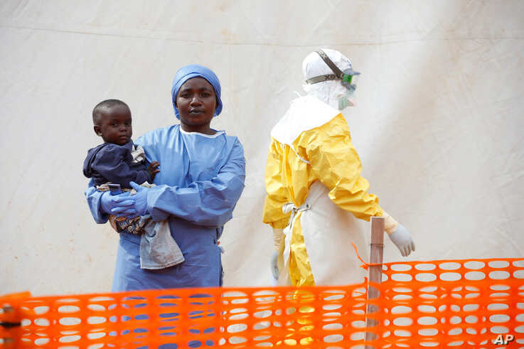 Mwamini Kahindo, an Ebola survivor working as a caregiver to babies who are confirmed Ebola cases, holds an infant outside the red zone at the Ebola treatment center in Butembo, Democratic Republic of Congo, March 25, 2019.