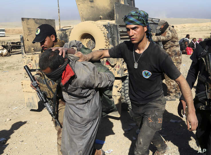 FILE - In this Feb. 25, 2017 file photo, Iraqi special forces arrest a suspected Islamic State fighter in Mosul, Iraq.