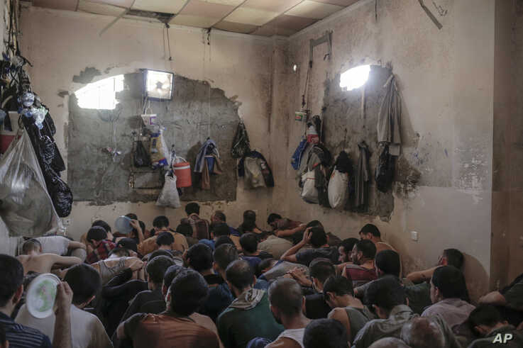 FILE - Suspected Islamic State members sit inside a small room in a prison south of Mosul, July 18, 2017.