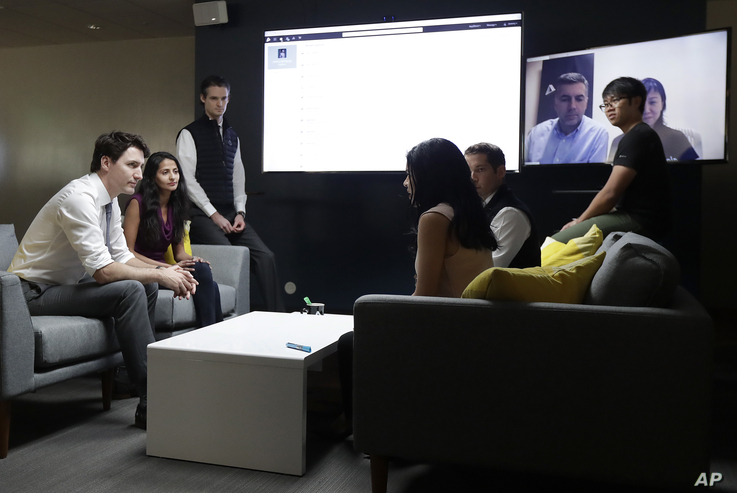 Canada's Prime Minister Justin Trudeau, left, speaks with AppDirect employees at their office in San Francisco, Feb. 8, 2018. Trudeau was pitching Canada as a destination for American tech firms amid increasing unease over U.S. immigration policy