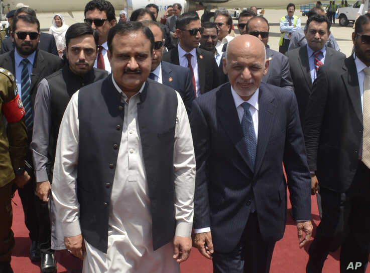 In this photo released by the Press Information Department, visiting Afghan President Ashraf Ghani, right, is received by the chief minister of Punjab province Usman Buzdar at Lahore airport in Pakistan, June 28, 2019.