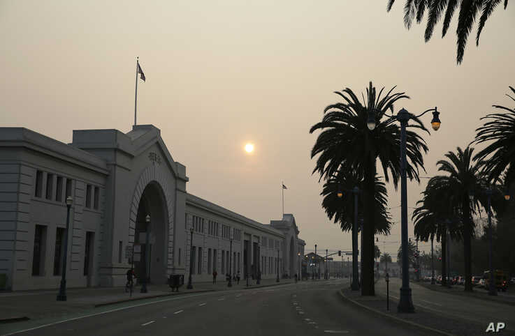 Smoke and haze from wildfires obscures the Embarcadero, Nov. 15, 2018, in San Francisco.