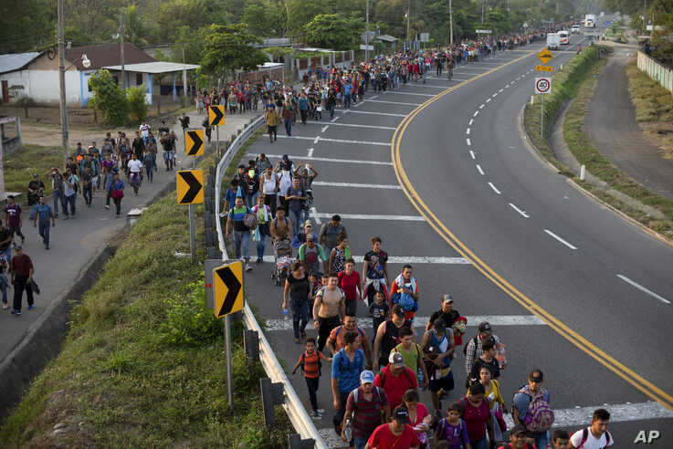 CORRECTS LOCATION - Central American migrants, part of the caravan hoping to reach the U.S. border, walk on the shoulder of a road in Frontera Hidalgo, Mexico, Friday, April 12, 2019. The group pushed past police guarding the bridge and joined a larger group of about 2,000 migrants who are walking toward Tapachula, the latest caravan to enter Mexico. (AP Photo/Isabel Mateos)