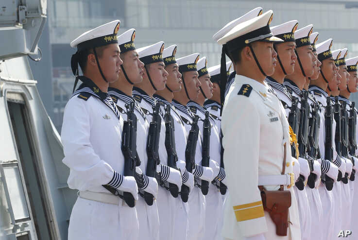 """Chinese People's Liberation Army Navy troops stand in formation on the deck of a type 054A guided missile frigate """"Wuhu"""" as it docks at Manila's South Harbor for a four-day port call, Jan. 17, 2019 in Manila, Philippines. Two other ships from the Chinese Naval Task Group """"Handan,"""" also a guided missile frigate and Dongpinghu, a replenishment or supply ship, arrived with """"Wuhu"""" in the second such visit of a China People's Liberation Army Navy or PLAN, under President Rodrigo Duterte's administration."""