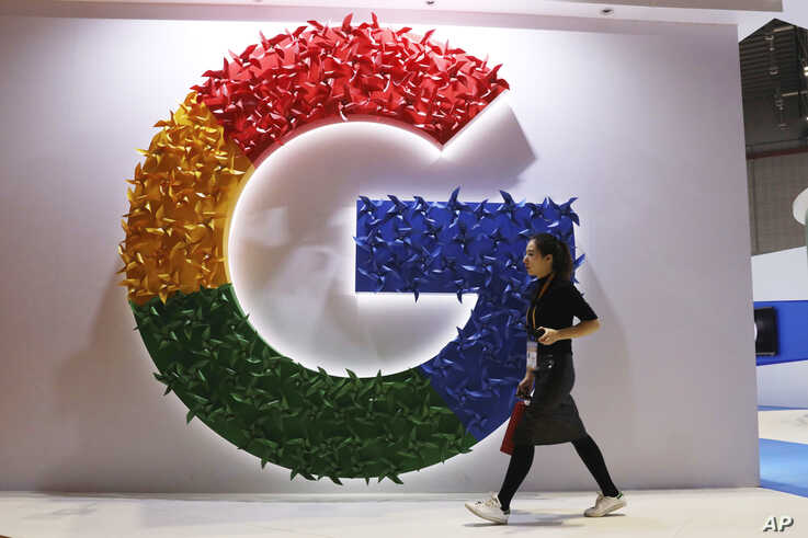 REPORT - A woman passes the Google logo at the China International Import Expo in Shanghai on November 5, 2018.