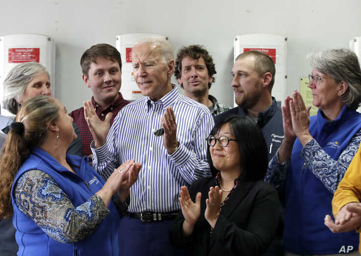 Former vice president and Democratic presidential candidate Joe Biden, center, is applauded as he speaks during a tour at the Plymouth Area Renewable Energy Initiative in Plymouth, N.H., June 4, 2019.