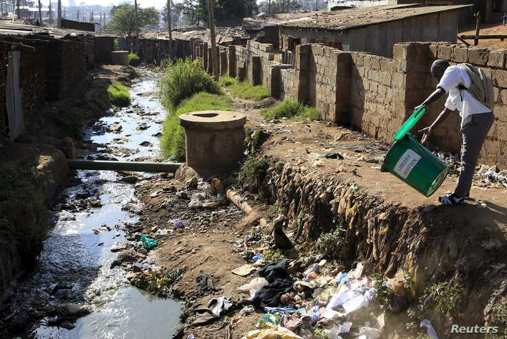 A student empties a dustbin next to a murky stream near a school in Kenya's Kibera slums in capital Nairobi, Sept. 21, 2015.