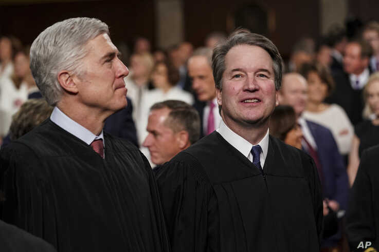 FILE - Supreme Court Associate Justices Neil Gorsuch, left, and Brett Kavanaugh watch as President Donald Trump arrives to give his State of the Union address to a joint session on Congress at the Capitol in Washington.