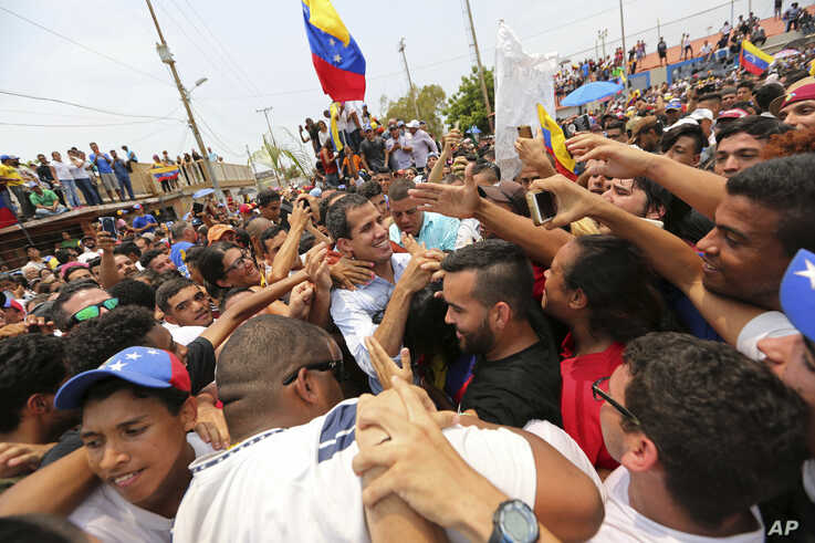 Juan Guaidó, opposition leader and self-proclaimed interim president of Venezuela, is surrounded by supporters at the end of a rally on the shore of Lake Maracaibo in Cabimas, Venezuela, April 14, 2019.