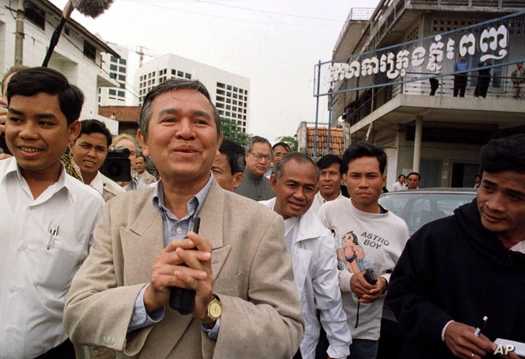 Kem Sokha, former chairman of the Cambodian parliament's human rights commission, center, greets the press as he leaves the Phnom Penh Municipal Court in Cambodia Tuesday, Dec. 15,1998.