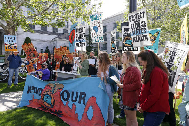 """Protesters gather outside the Utah Governor's Energy Summit at Grand America Hotel, May 30, 2019, in Salt Lake City. U.S. Energy Secretary Rick Perry spoke a the energy summit hosted by Utah Gov. Gary Herbert and attended by Wyoming Gov. Mark Gordon. The Trump administration is committed to making fossil fuels cleaner rather than imposing """"draconian"""" regulations on oil, gas and coal, Perry said. (AP Photo/Rick Bowmer)"""
