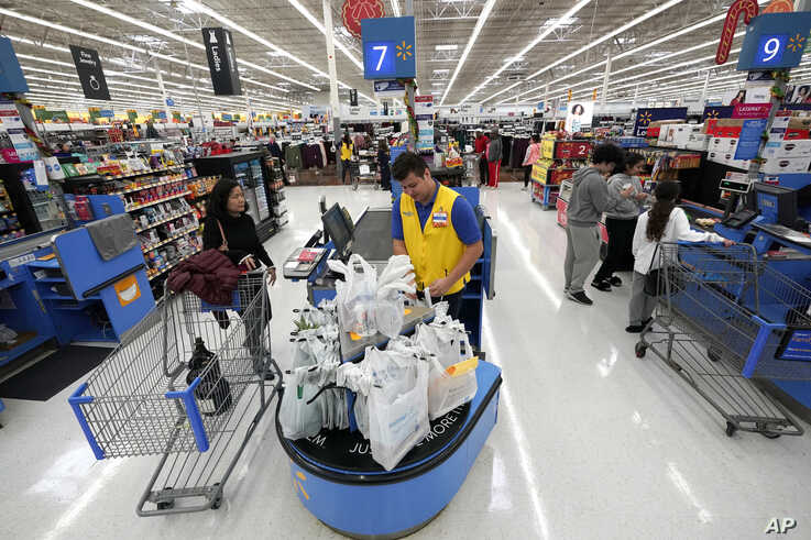 FILE- In this Nov. 9, 2018, file photo Walmart associate Luis Gutierrez, center, checks out a customer at a Walmart Supercenter in Houston. On Thursday, Jan. 31, 2019, the Labor Department releases the employment cost index for the fourth quarter, a measure of wage and benefit growth. (AP Photo/David J. Phillip, File)