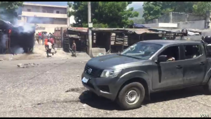 A gray pickup truck with armed men wearing police uniforms who shot tear gas and rubber bullets at protesters.