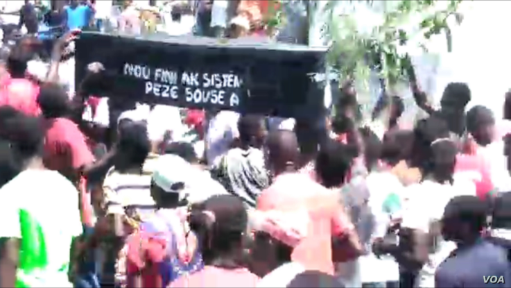 """Protesters in Les Cayes march with a coffin with words that read """"We are done with this repressive, predatory system""""."""