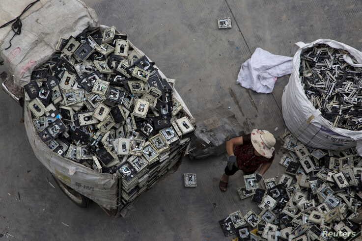 FILE - A worker distributes electronic waste at a government managed recycling center at the township of Guiyu in China's southern Guangdong province, June 10, 2015.