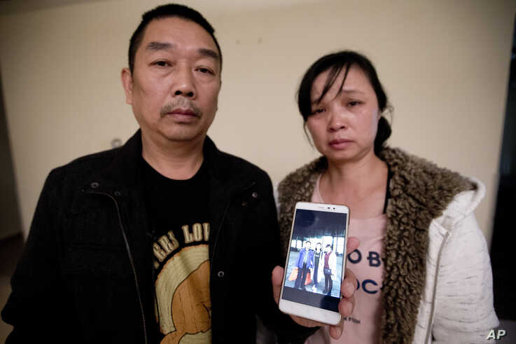 FILE - Ronggao Zhang, left, and Lifeng Ye, display a photo them with their missing daughter, Yingying Zhang, in Urbana, Ill., Nov. 1, 2017.