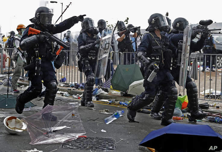 A policeman fires with a pepper ball gun towards protesters near the Legislative Council in Hong Kong, June 12, 2019.