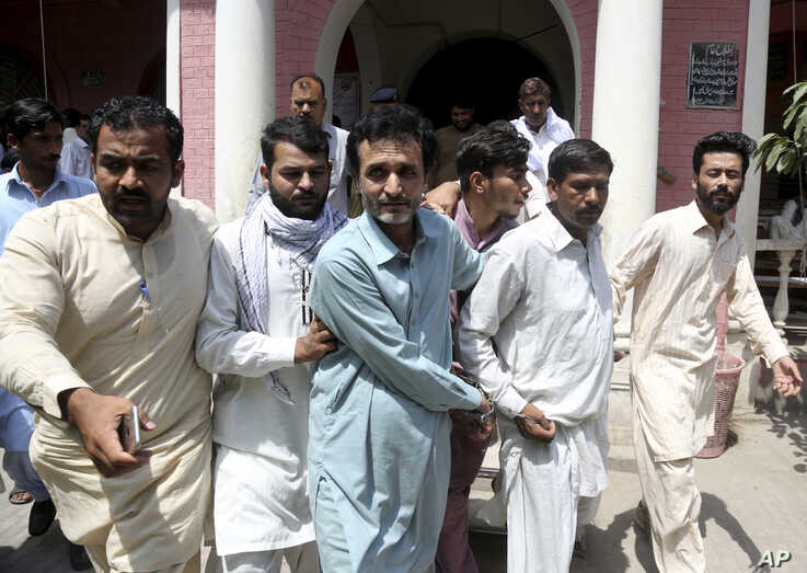 Officials of Pakistan's Federal Investigation Agency escort detained criminals allegedly involved in a trafficking gang to lure Pakistani women into fake marriages, to a court in Faisalabad, May 15, 2019.