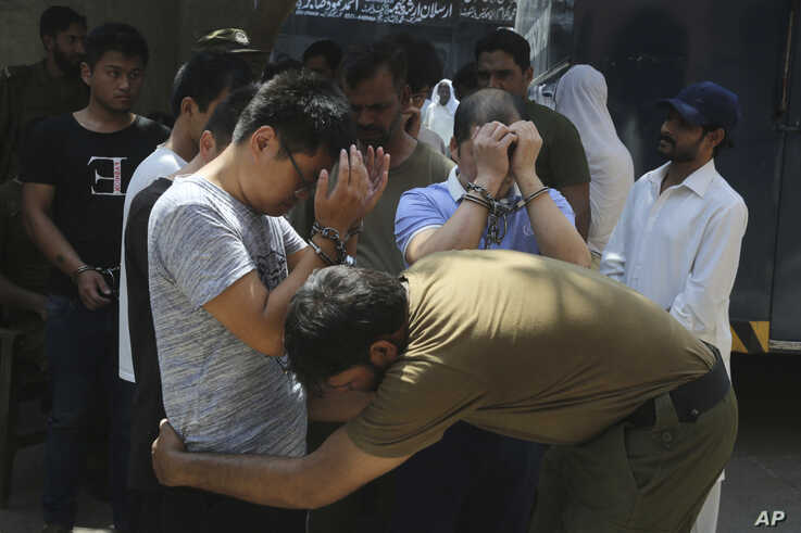 A police officer searches detained Chinese nationals, who are alleged to be involved in a trafficking gang to lure Pakistani women into fake marriages, as they arrive to a court in Lahore, Pakistan, June 10, 2019.