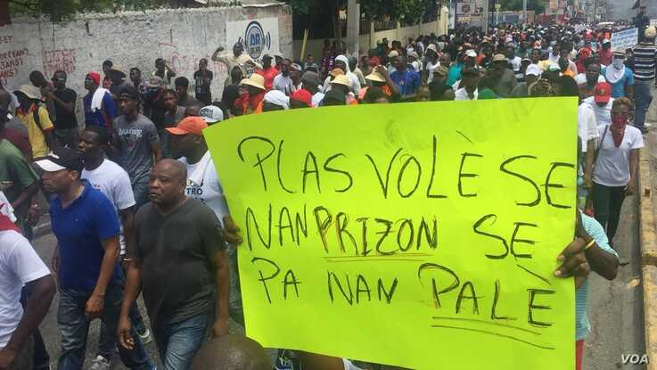 "A protester holds poster that reads ""Thieves belong in jail, not in the palace,"" in Port-au-Prince, Haiti, June 9, 2019."