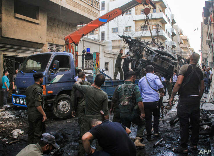 Syrian Kurdish security forces lift the wreckage of a rigged car which detonated outside the Syriac Orthodox Church of the Virgin Mary in Qamishli in northeast Syria, July 11, 2019.