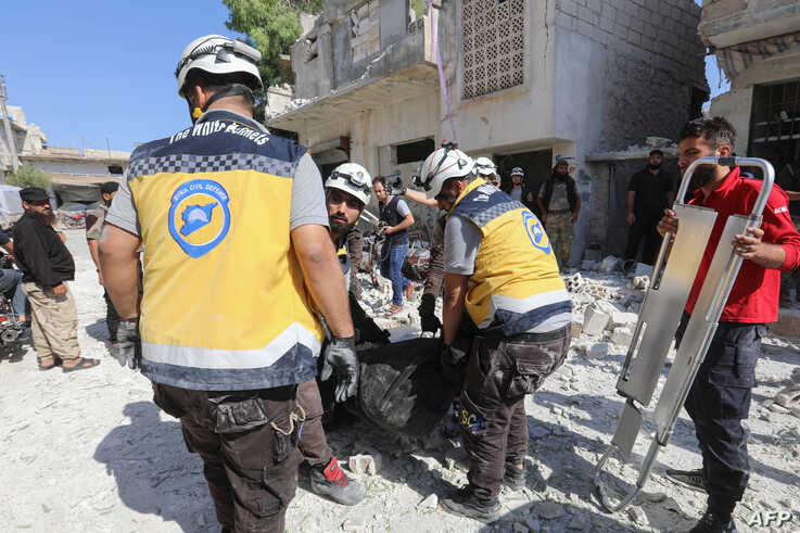 Members of the Syrian Civil Defense carry away a body retrieved from the rubble following a reported regime airstrike on the village of Kafriya, in Syria's Idlib province, July 13, 2019.