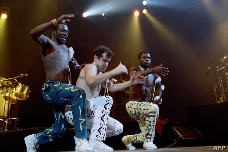 FILE - South African singer Johnny Clegg, center, and dancers of South African band Savuka perform on stage at the Zenith concert hall in Paris as part of three-concert series dedicated to the fight against apartheid, May 10, 1988.