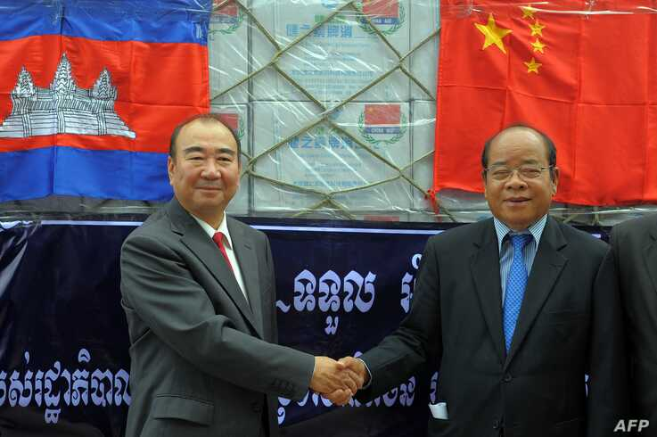 Chinese Ambassador to Cambodia Pan Guang Xue, left, shakes hands with Cambodian first vice president of the National Committee for Disaster Management Nhim Vanda at Phnom Penh international airport, Oct. 15, 2011.