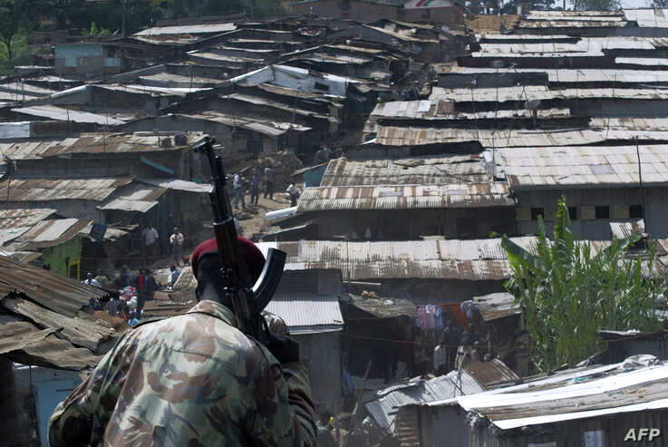 FILE - A member of the police enters Mathare, a slum in Nairobi, Kenya, June 7, 2007.
