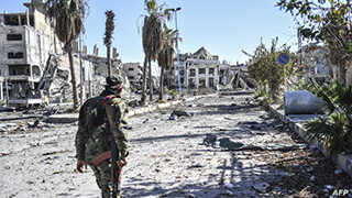 A member of the Syrian Democratic Forces (SDF) walks through a heavily damaged street leading to an Armenian church in Raqqa, Syria, Oct. 18, 2017.