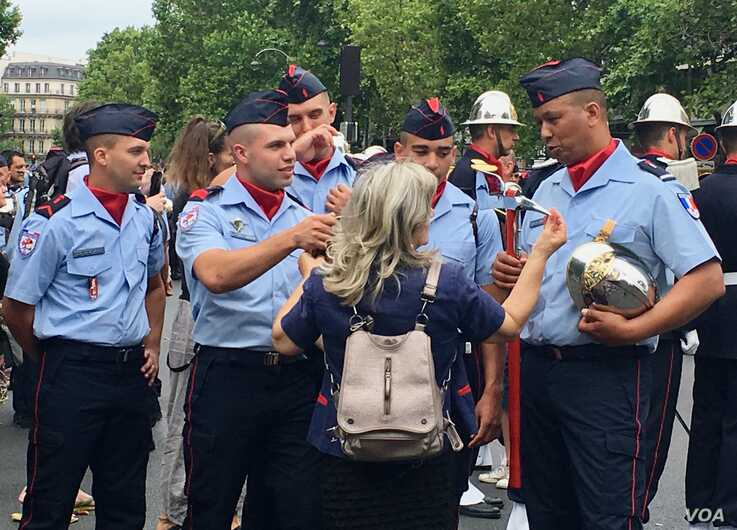 A woman talks to French forces after the Bastille Day parade, in Paris, France, July 14, 2019. (L. Bryant/VOA)